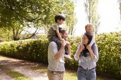 Padres que dan a hijos paseo en hombros durante paseo fotos de archivo