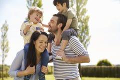 Padres que dan a hijos paseo en hombros durante paseo imágenes de archivo libres de regalías