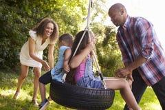 Padres que empujan a niños en el oscilación del neumático en jardín Fotografía de archivo