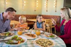 Padres que hablan con los niños en restaurante Imagen de archivo libre de regalías