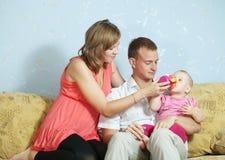 Padres que introducen a su bebé con la botella Fotos de archivo