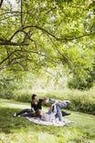 Padres que juegan con el toodler en la manta Foto de archivo libre de regalías