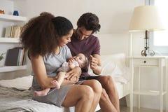 Padres que juegan con la hija del bebé en dormitorio en casa Fotos de archivo libres de regalías