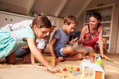 Padres que juegan con los niños y los juguetes en una sala de juegos del ático imagen de archivo