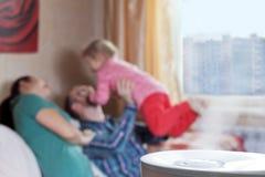Padres que juegan con su hija en el fondo del humidif Foto de archivo