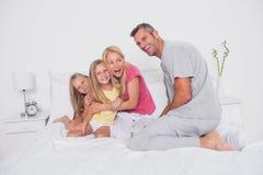 Padres que juegan en cama con sus gemelos Imagenes de archivo