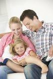 Padres que leen con la hija en casa imagen de archivo libre de regalías