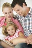 Padres que leen con la hija en casa fotografía de archivo libre de regalías