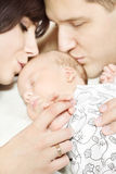 Padres que llevan a cabo la mano recién nacida del bebé, besando al niño fotografía de archivo