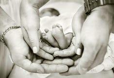 Padres que llevan a cabo pies del bebé en sus manos Fotos de archivo libres de regalías