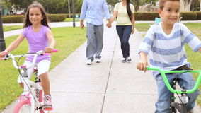 Padres que llevan a niños a las bicis del paseo en parque metrajes