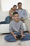 Padres que miran al hijo jugar a los videojuegos en vista delantera de la sala de estar Foto de archivo