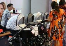 Padres que miran los carros de bebé imagen de archivo