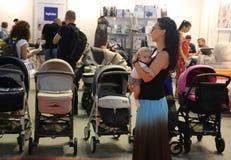 Padres que miran los carros de bebé Imagenes de archivo