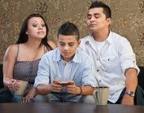 Padres que miran mensajes de envío adolescentes Imagenes de archivo