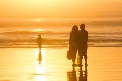 Padres que miran siluetas del niño en la puesta del sol en la playa Foto de archivo