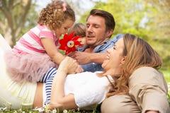 Padres que se sientan con los niños en campo Imágenes de archivo libres de regalías