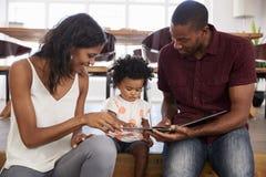 Padres que se sientan y que leen con la hija en casa imagenes de archivo