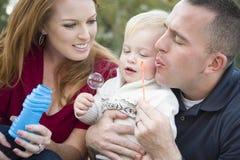 Padres que soplan burbujas con el muchacho del niño en parque Fotos de archivo