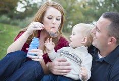 Padres que soplan burbujas con su niño en parque Fotografía de archivo