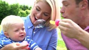 Padres que soplan las burbujas para el muchacho joven en jardín almacen de metraje de vídeo