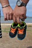 Padres que sostienen el zapato de bebé en la playa Imágenes de archivo libres de regalías