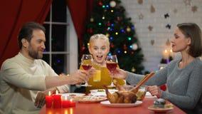 Padres que tintinean el vino el víspera de Navidad, jugo de consumición del niño, familia feliz que celebra almacen de metraje de vídeo