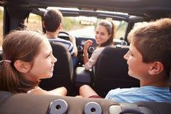 Padres que toman a niños en viaje en coche de tragante abierto imagenes de archivo