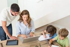 Padres que usan el ordenador portátil mientras que niños que colorean en casa imágenes de archivo libres de regalías