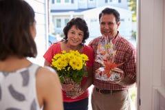 Padres que visitan a la hija hispánica en nuevo hogar fotos de archivo