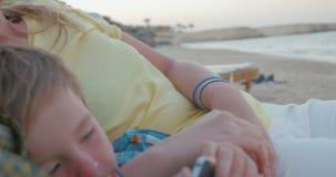 Padres relajados y niño con la célula en la playa almacen de video