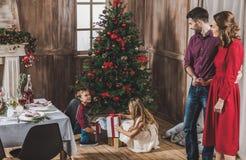 Padres sonrientes que miran a niños imagen de archivo libre de regalías