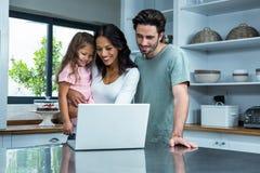 Padres sonrientes que usan el ordenador portátil con la hija Fotografía de archivo