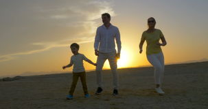 Padres y baile del hijo en la puesta del sol almacen de metraje de vídeo