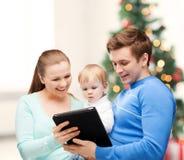 Padres y bebé adorable con PC de la tableta Imágenes de archivo libres de regalías