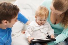 Padres y bebé adorable con PC de la tableta Fotos de archivo libres de regalías