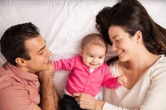 Padres y bebé en una cama Fotos de archivo libres de regalías