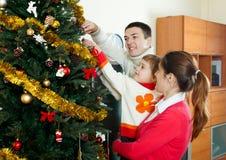 Padres y bebé que adornan el árbol de navidad Imagen de archivo
