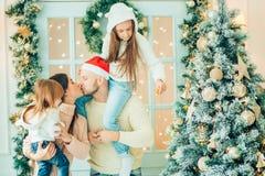 Padres y bebé que se divierten cerca del árbol de navidad Familia cariñosa por el árbol de navidad Imagenes de archivo
