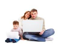 Padres y cabrito con la computadora portátil Imagen de archivo
