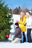 Padres y cabritos que adornan el árbol de navidad Imágenes de archivo libres de regalías
