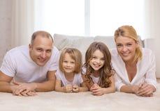 Padres y dos muchachas que mienten en piso en casa Foto de archivo