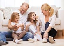 Padres y dos muchachas que se sientan en piso en casa Imagen de archivo libre de regalías
