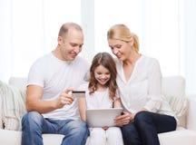 Padres y muchacha con PC de la tableta y la tarjeta de crédito Foto de archivo libre de regalías