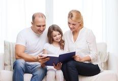 Padres y niña sonrientes con en casa Fotografía de archivo