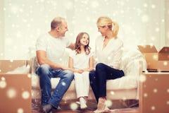 Padres y niña sonrientes en el nuevo hogar fotografía de archivo