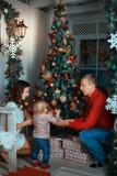 Padres y niño cerca de un árbol de navidad Fotos de archivo