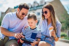 Padres y niño pequeño sonrientes con PC de la tableta fotografía de archivo
