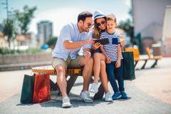 Padres y niño pequeño sonrientes con PC de la tableta y la tarjeta de crédito fotos de archivo libres de regalías