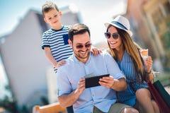 Padres y niño pequeño sonrientes con PC de la tableta y la tarjeta de crédito imagen de archivo